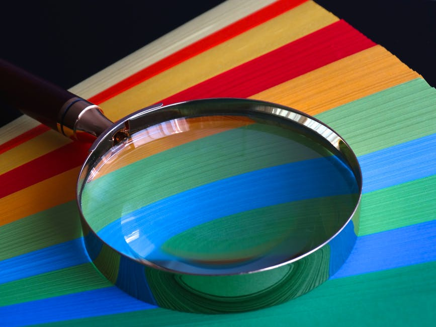 magnifying glass and colorful file folders