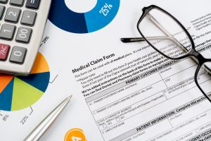 medical claim form with glasses and calculator