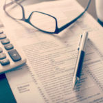 Tax forms, calculator, glasses and pen